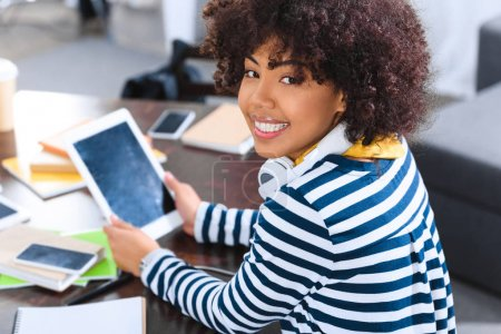 smiling african american student with headphones and tablet sitting at table