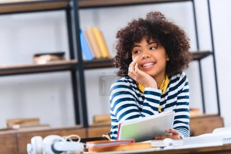 portrait of dreamy african american student looking away while studying alone