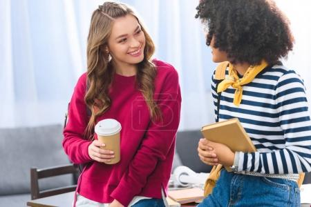 smiling multiethnic students with backpacks having conversation