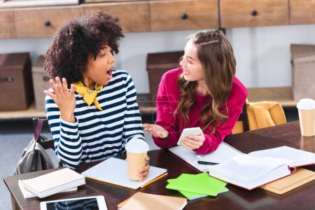 portrait of multicultural students with smartphone studying together