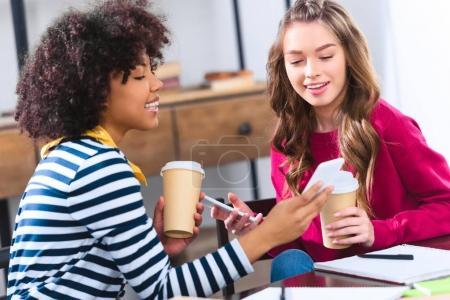 smiling multicultural students using smartphone together