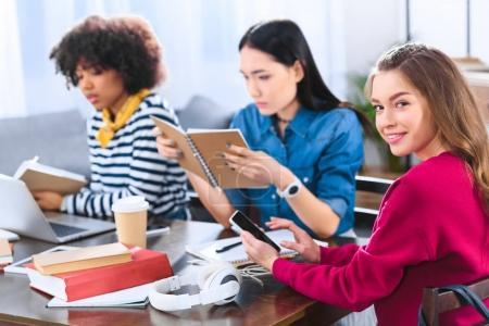 Photo pour Foyer sélectif de sourire jeune femme avec smartphone et étudiants multiethniques à proximité - image libre de droit