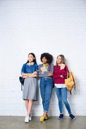 young multiracial students standing against white brick wall