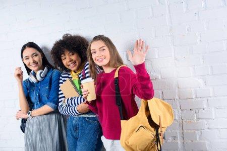 Photo pour Portrait d'étudiants multiraciaux souriants debout contre un mur de briques blanches - image libre de droit