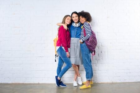 asian student hugging smiling multiethnic friends against white brick wall