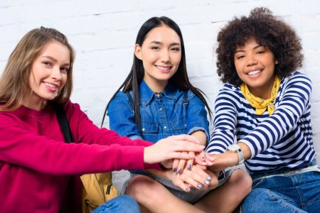 portrait of smiling multicultural students holding hands together