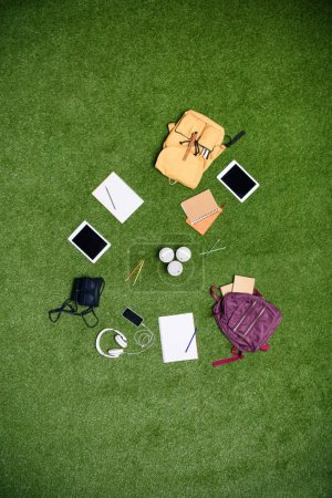 top view of arranged digital devices, backpacks and notebooks on green lawn