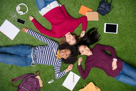 Photo for Overhead view of cheerful multicultural students lying on green lawn - Royalty Free Image