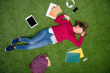 overhead view of young student sleeping on green lawn
