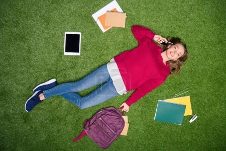overhead view of young student talking on smartphone while resting on green lawn