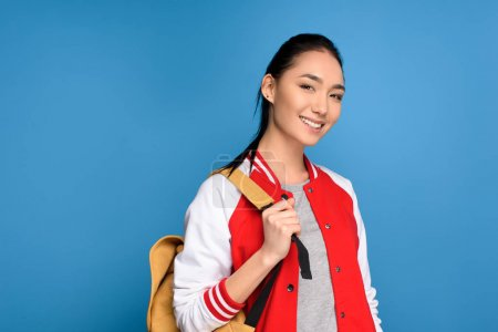 portrait of smiling asian student with backpack isolated on blue