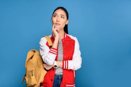 portrait of pensive asian student with backpack isolated on blue