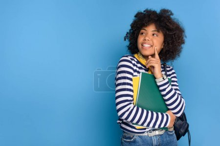 Photo for Portrait of cheerful african american student with notebooks isolated on blue - Royalty Free Image