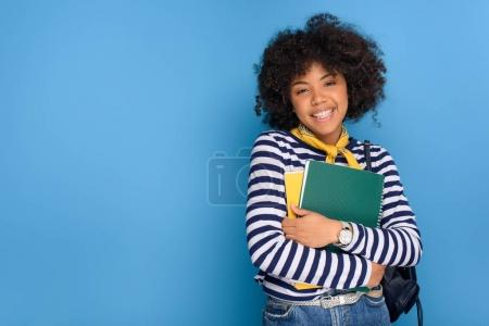 portrait of cheerful african american student with notebooks isolated on blue