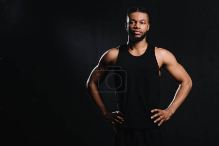 confident african american sportsman standing with hands on waist isolated on black
