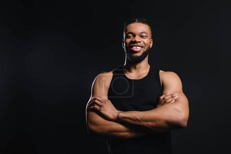 handsome smiling young african american sportsman standing with crossed arms isolated on black
