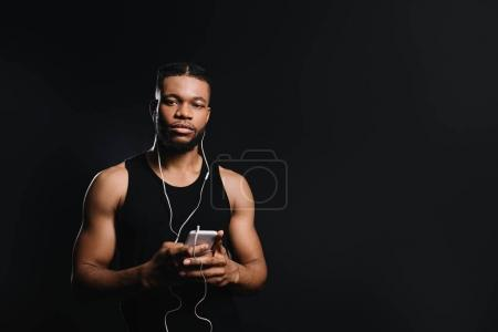 young african american sportsman in earphones holding smartphone and looking at camera isolated on black