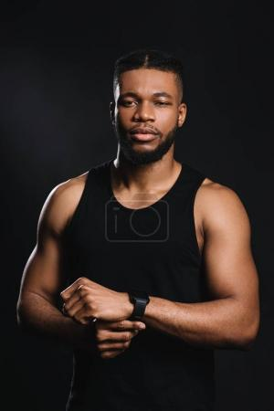 young african american sportsman using smartwatch and looking at camera isolated on black
