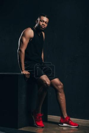 Photo for Full length view of handsome young african american sportsman sitting and looking at camera - Royalty Free Image