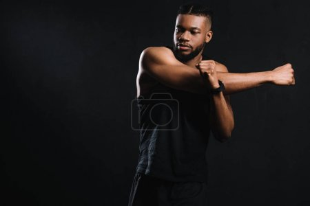 handsome athletic african american man stretching hands isolated on black