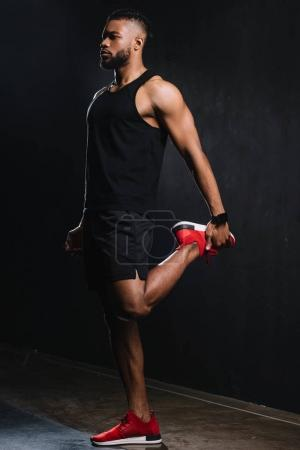 full length view of young african american sportsman stretching muscles on black