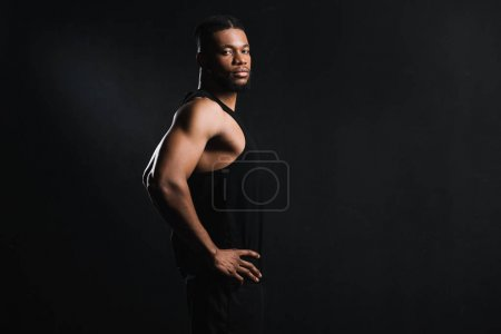 side view of athletic young african american man standing with hands on waist and looking at camera isolated on black