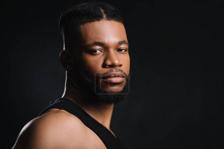 portrait of handsome young athletic african american man looking at camera isolated on black