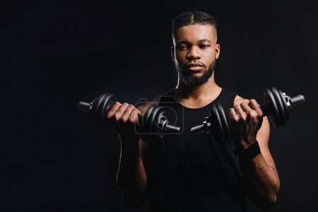 handsome young sportsman holding dumbbells and looking at camera isolated on black