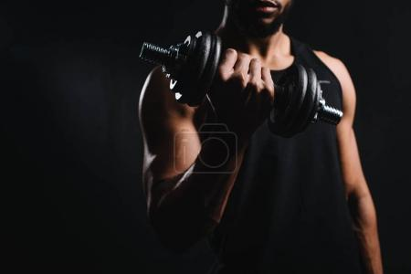 Photo for Cropped shot of muscular african american man exercising with dumbbell isolated on black - Royalty Free Image