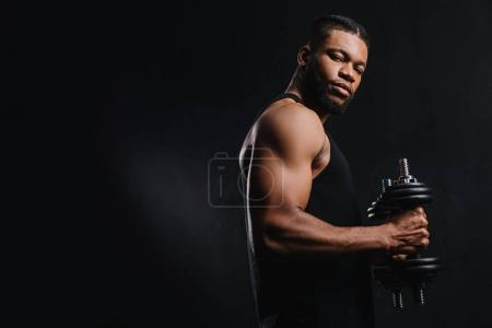 Photo for Muscular african american sportsman holding dumbbells and looking at camera isolated on black - Royalty Free Image