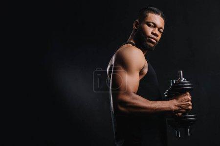 Photo pour Musculaire sportif africain-américain tenant des haltères et regardant la caméra isolée sur fond noir - image libre de droit