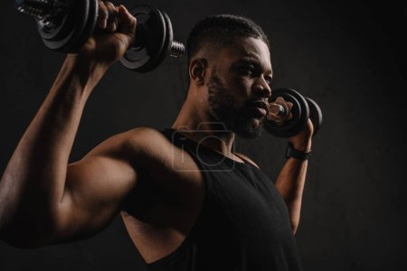 concentrated muscular african american man exercising with dumbbells isolated on black