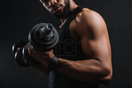Photo for Cropped shot of muscular african american sportsman exercising with dumbbells on black - Royalty Free Image