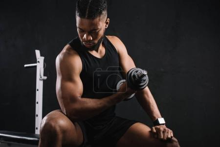 young african american sportsman exercising with dumbbell and looking at biceps