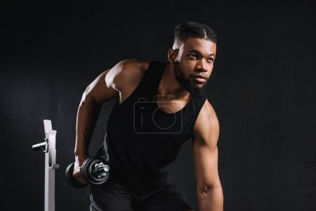 young african american sportsman exercising with dumbbell and looking away on black