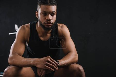 handsome young african american sportsman sitting and looking away on black