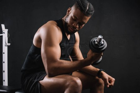 muscular young african american man exercising with dumbbell on black