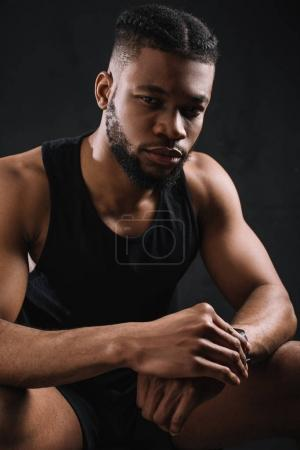 handsome young african american sportsman looking at camera on black
