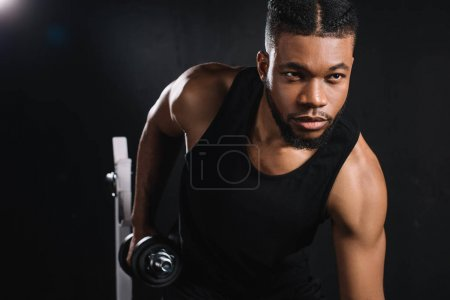 handsome young african american sportsman exercising with dumbbell in gym