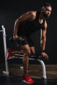 handsome muscular african american man in sportswear training with dumbbell and looking away