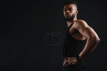 side view of athletic young african american man in sportswear looking at camera isolated on black