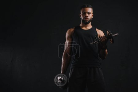 young african american sportsman exercising with dumbbells and looking at camera isolated on black