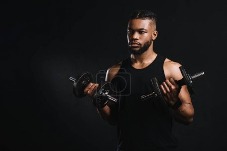 young african american sportsman exercising with dumbbells and looking away isolated on black