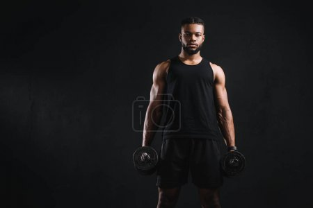 Photo for Young muscular african american sportsman holding dumbbells and looking at camera isolated on black - Royalty Free Image