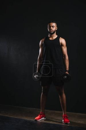 Photo for Full length view of young muscular african american sportsman holding dumbbells on black - Royalty Free Image