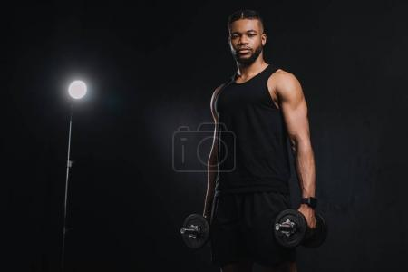 young african american sportsman holding dumbbells and looking at camera on black