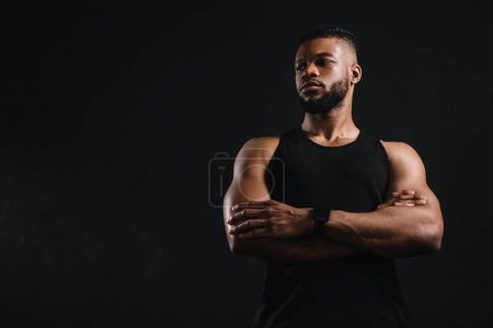 low angle view of confident african american sportsman standing with crossed arms and looking away isolated on black