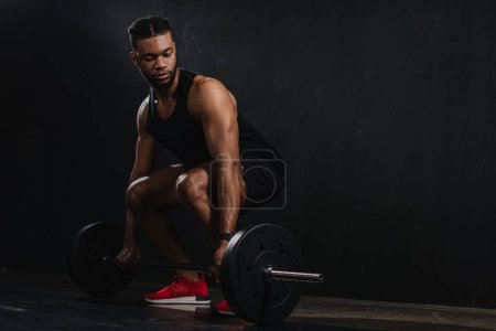 full length view of young african american sportsman lifting barbell on black