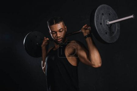 muscular young african american sportsman lifting barbell and looking at biceps on black