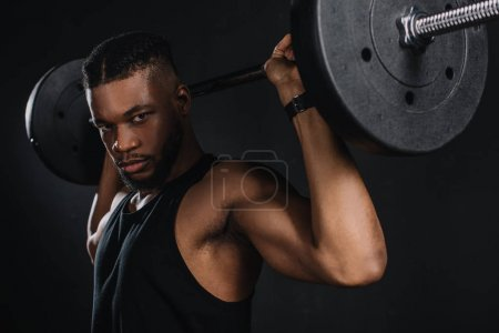 muscular young african american sportsman lifting barbell and looking at camera on black